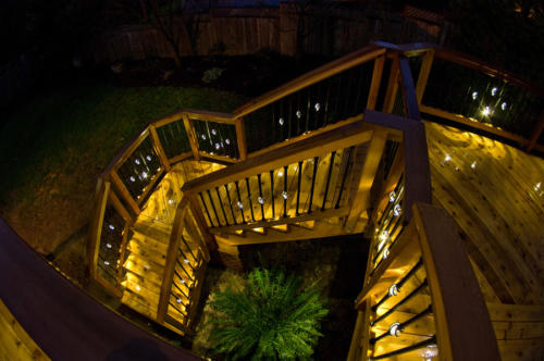 Deck stairs illuminated by balusters with LED lights