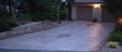 LED landscape lights: DEKOR Dek Dots illuminate a stamped concrete driveway at night